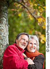 Happy old couple laughing while looking at something in the...