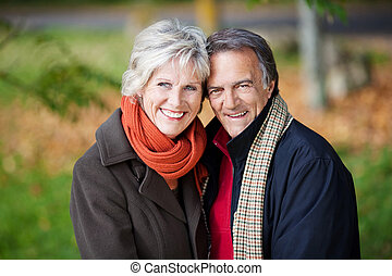 Happy mature couple posing over the outdoors background
