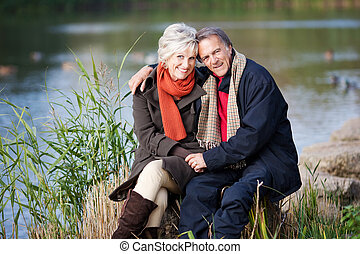 A senior couple posing by the lake