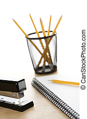 Office supplies on desk. - Pencils, a stapler, and spiral...