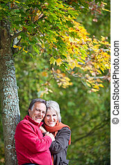 A happy senior couple posing at a forest