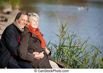 Happy senior couple enjoying the sun near a lake - A happy...