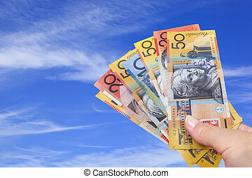 Handful of Australian Money over Blue Sky. - Handful of...