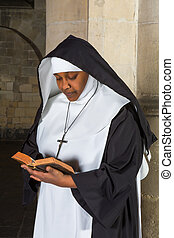 Praying nun - Mature nun reading the bible in a medieval...