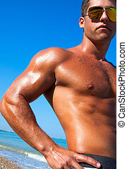 Muscular brutal man on the beach - A man with a beautiful...
