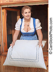 make beds - Young peasant woman in dirndl shakes the beds on...