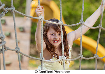 girl climbing on a net at playground