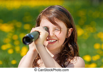 Girl Looking Through Telescope In Park - Closeup of happy...