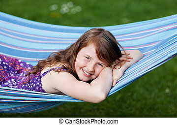 Girl Lying On Hammock In Park - Portrait of young girl lying...