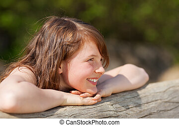 girl leaning relaxed on tree trunk while looking away
