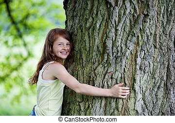 cute little girl hugging tall tree - waist-up portrait of a...