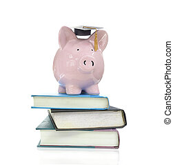 books and piggy - piggy bank with graduation cap on a pile...