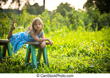 Charming little girl in the yard of a country house