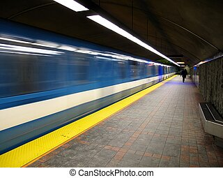 A subway leaving a station with people walking