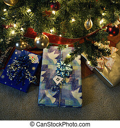 Christmas presents under tree. - Christmas presents under...