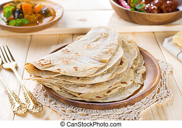 Chapatti roti or Flat bread, curry chicken and dhal. Indian...