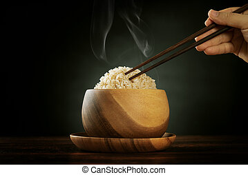 Cooked organic basmati brown rice with steam and chopsticks...
