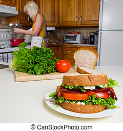 Home cooking - A blt sandwich with a woman cooking in the...