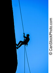 Silhouette of Man Rappelling