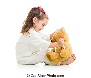 child girl with clothes of doctor playing with toy