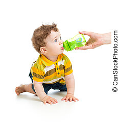 adorable child drinking from bottle. 8 months old boy.
