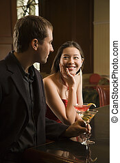 Couple at bar. - Taiwanese mid adult woman and Caucasian man...
