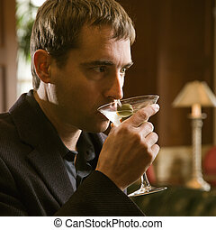 Man drinking martini - Mid adult Caucasian man drinking...