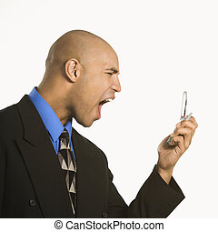Man yelling at cellphone - Head and shoulder portrait of...