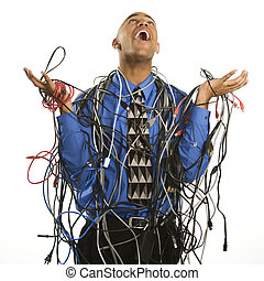 Man wrapped in cables - African American businessman wrapped...
