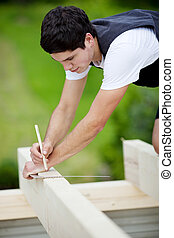 Carpenter making markings on a roof beam using a pencil and...