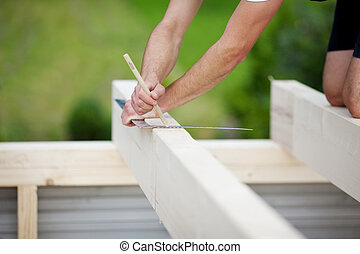 Close-up of a carpenter making markings on a beam