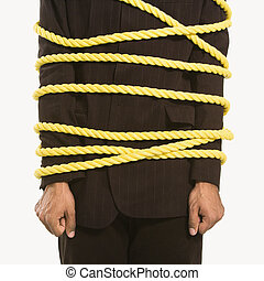 Businessman tied in rope - African American businessman...