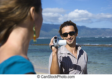 Couple with video camera. - Mid-adult Caucasian man on beach...
