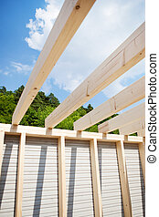 Roof beams of an unfinished roof with trees and sky in the...