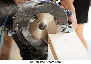 Close-up of a carpenter using a circular saw to cut a large...