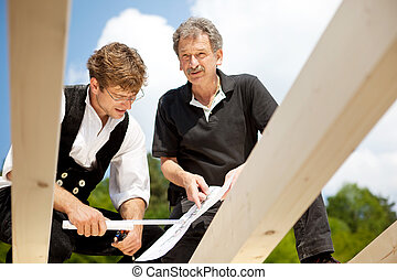 Architect and carpenter discussing the blue prints standing...
