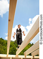 Carpenter standing on the roof beams - Carpenter standing...