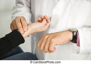 Doctor taking patient's pulse.