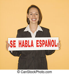 Businesswoman holding bilingual sign. - Caucasian...
