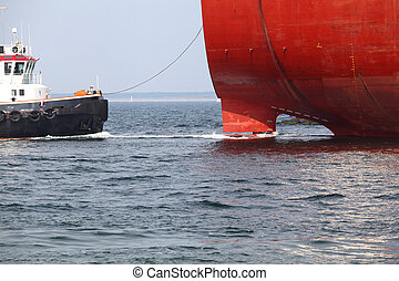 Docking Maneuver - A tugboat takes a cargo vessel on the...