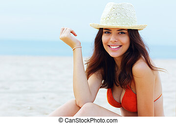 Young beautiful happy woman resting on the beach