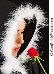 Portrait of sad woman in black cape and rose artistic...