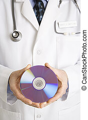 Doctor holding compact disc - Close up of Caucasian mid...
