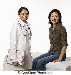 Doctor and patient - Indian woman doctor with Asian woman...