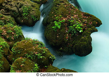 rocks on tourquoise stream - rock on stream with view of...