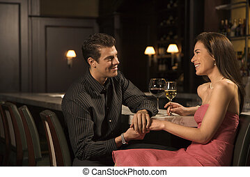 Couple at bar. - Mid adult Caucasian couple at bar holding...