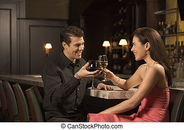 Couple at bar. - Mid adult Caucasian couple at bar toasting...