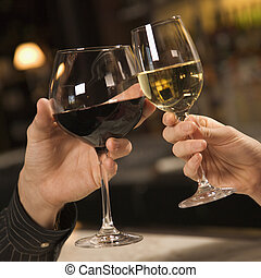 Hands toasting wine - Mid adult Caucasian male and female...