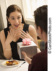 Man giving woman gift. - Mid adult Caucasian man presenting...