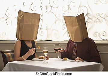 Couple wearing bags. - Mid adult Caucasian couple dining in...